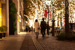 People walking down the street lit with Christmas lights